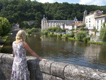 Tourist on bridge viewing historic building, Brantome, Dordogne, France Royalty Free Stock Photography