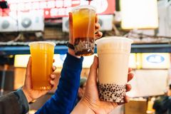 Tourist bring up Bubble Milk Teas in the air, street food at Ximending in Taipei, Taiwan.  royalty free stock photography