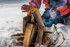 The tourist builds a fire in the winter forest. And heats his hands Royalty Free Stock Photo