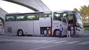 Tourist bus boarding. Group of tourists board bus in stop action time lapse ending of two passengegers running after pulling away transporter. people stock video