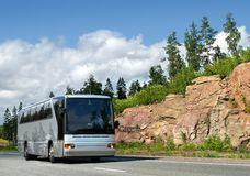 Tourist bus on country highway. Tourist bus on rocky highway Scandinavia, landscape Royalty Free Stock Images