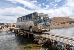 Tourist Bus Crossing River - Ayaviri, Peru. AUGUST 16, 2006 - PUKARA, PERU: Tourist bus crossing a wooden bridge over a small river Royalty Free Stock Image