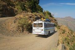 Tourist bus pass by the gravel mountain road in Axum, Ethiopia. Stock Photos