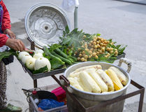 Tourist is buying boiled corn at local market. Woman is selling boiled corns and fresh wampee fruit Royalty Free Stock Photo