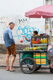 Tourist buys cut fruit Royalty Free Stock Images