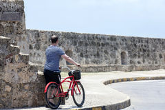 Tourist and Bycicle in Cartagena de Indias. CARTAGENA, COLOMBIA - JULY 2015. Tourist man with a bicycle in Cartagena de Indias Royalty Free Stock Photography