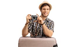 Tourist with a camera leaning on a suitcase Stock Photo