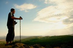 Tourist with camera on neck and poles in hands on peak of rock. Dreamy landscape bellow  in a beautiful valley below Royalty Free Stock Photos