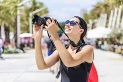 Tourist with a camera photographing the streets on a sunny day. Royalty Free Stock Image