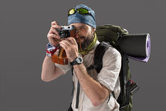 Tourist with camera. The tourist with camera. Portrait of a male fully equipped tourist with backpack. He photographing something on gray background Royalty Free Stock Photography