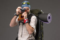 Tourist with camera. The tourist with camera. Portrait of a male fully equipped tourist with backpack. He photographing something on gray background Stock Image