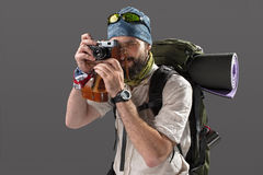 Tourist with camera. The tourist with camera. Portrait of a male fully equipped tourist with backpack. He photographing something on gray background Stock Photos