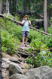 Tourist with camera in the Rocky Mountains. A male tourist, camera in hand, braves a rocky ledge in the Colorado Rocky mountains, eager to get that perfect photo Stock Photos