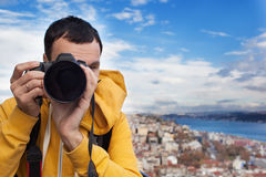 Tourist with camera take a picture. Tourist with a camera photographing landscape in Istanbul, Turkey. Landscape looked like a classic European city Stock Image