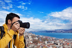Tourist with camera take a picture. Tourist with a camera photographing landscape in Istanbul, Turkey. Landscape looked like a classic European city Royalty Free Stock Photography