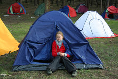 Tourist camp. The girl sits in tent Royalty Free Stock Photos