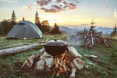 Tourist camp with fire, gree tent and firewood. Tourist camp with fire, tent and firewood Stock Photo
