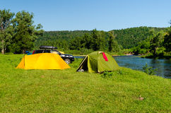 Tourist camp with tents and car. On the river bank stock photos