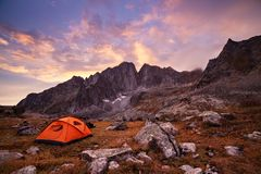 Tourist camping in the mountains. Tent in mountains at beautiful sunrise Royalty Free Stock Image