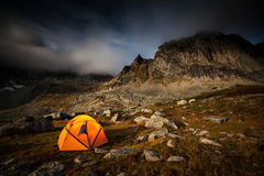 Tourist camping in the mountains. Tent near mountain at moon night Stock Photo