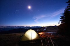 Tourist camping near forest in the mountains. Illuminated tent and campfire under evening sky full of stars and the moon Stock Photos