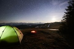 Tourist camping near forest in the mountains. Illuminated tent and campfire under night sky full of stars and the moon Stock Images