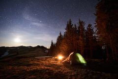 Tourist camping near forest in the night. Illuminated tent and campfire under night sky full of stars and the moon Royalty Free Stock Images