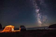 Tourist camping at sea coast at night with milky way. Some noise from hugh iso exists royalty free stock photography