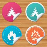 Tourist camping tent signs. Fire flame icons. Round stickers or website banners. Tourist camping tent icons. Fire flame sign symbols. Circle badges with bended Royalty Free Stock Image