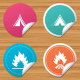 Tourist camping tent signs. Fire flame icons. Round stickers or website banners. Tourist camping tent icons. Fire flame sign symbols. Circle badges with bended Royalty Free Stock Photos