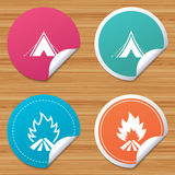 Tourist camping tent signs. Fire flame icons. Round stickers or website banners. Tourist camping tent icons. Fire flame sign symbols. Circle badges with bended Royalty Free Stock Images