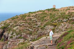 Tourist at Cap Fréhel. Beautiful young tourist on the edge of the cliffs at Cap Fréhel in Brittany, France, with the old lighthouse in the background Stock Photography