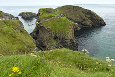 Tourist on the Carrick-a-Rede rope bridge on the Causeway Coast in Antrim County, N. Orthern Ireland stock photo