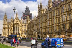 Tourist and cars in front of Westminster Houses of Parliament. royalty free stock images