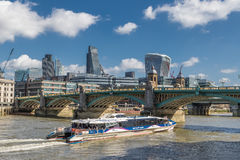 Tourist catamaran boat floats near Southwark bridge. LONDON, UK - MARCH 25, 2016: Tourist catamaran boat floats towards Southwark Bridge with 'Walkie Talkie' royalty free stock photos