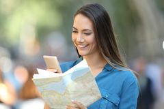 Tourist checking destination in a smart phone and map Royalty Free Stock Photos