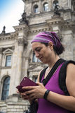 Tourist checking her smartphone in front of Reichstag. A tourist checking her smartphone in front of Reichstag building in Berlin, Germany Royalty Free Stock Photos
