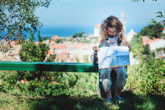 Tourist child girl with map traveling on summer vacations in Piran Stock Photos