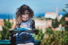 Tourist child girl with map traveling on summer vacations in Piran. Slovenia Royalty Free Stock Photos