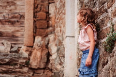 Tourist child girl at stone wall on the walk in Piran, Slovenia Stock Images