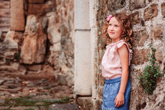 Tourist child girl at stone wall on the walk in Piran, Slovenia Stock Photography