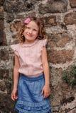 Tourist child girl at stone wall on the walk in Piran, Slovenia Royalty Free Stock Photo