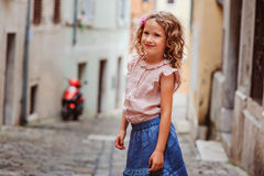 Tourist child girl at stone wall on the walk in Piran, Slovenia Stock Photos