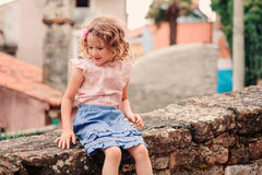 Tourist child girl at stone wall on the walk in Piran, Slovenia Royalty Free Stock Photography