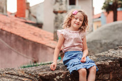 Tourist child girl at stone wall on the walk in Piran, Slovenia Royalty Free Stock Images