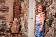 Tourist child girl at stone wall on the walk in Piran, Slovenia Royalty Free Stock Photos