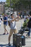 Tourist from China makes selfy in the central Dam Square in Amsterdam. Amsterdam, Netherlands - July 02, 2018: Tourist from China makes selfy in the central Dam royalty free stock photos