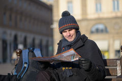 Tourist with city plan. On a bench at winter Stock Image