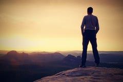 Tourist on cliff of  mountain summit. Outdoor activites. Royalty Free Stock Image