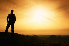 Tourist on cliff of  mountain summit. Outdoor activites. Stock Image